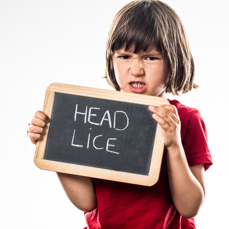 head protection: angry young child holding a school slate as a protection shield against head lice for preschooler healthcare fight, white background studio Stock Photo