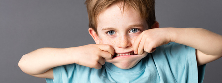 misbehave: happy little kid with blue eyes and freckles having fun, playing with his mouth to make it big for freedom and silly childhood, grey background Stock Photo
