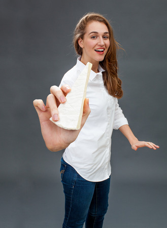 dairy product: smiling young beautiful woman having fun in holding a healthy dairy product in her hand in the foreground, grey background studio
