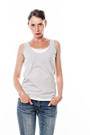 tied hair: sulking beautiful young woman with tied hair standing with hands in jeans pockets to disagree or show her frustration, white background