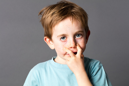 misbehave: fun 5-year old boy with blue eyes and freckles making an ugly grimace, pulling his eyes down to be a monster, grey background