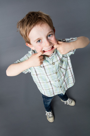 misbehavior: smiling red hair young child standing, making a funny face with his big mouth for comical misbehavior, high angle view, grey background
