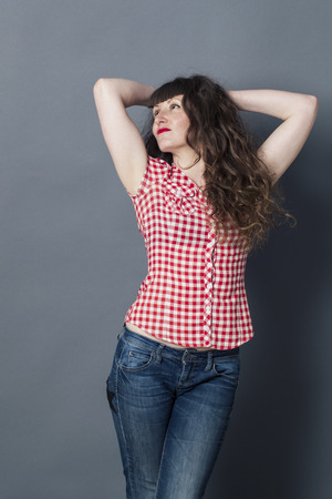 seductive young woman with long curly brown hair holding back her arms behind her head for proud femininity, grey background studio Stock Photo