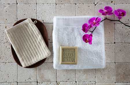 mitt: genuine toiletries concept with French mitt, organic olive oil Marseilles soap, white cotton towel with pink orchid set on pure beige limestone, flat lay, top view