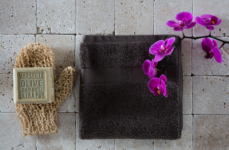 mitt: exfoliating concept with body mitt, olive oil soap, dark grey cotton towel with pink orchid set on clean beige limestone for body care, flat lay, top view
