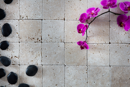 beauty spa wallpaper with feng shui black massage pebbles and beautiful pink orchids set on natural limestone background for copy space, flat lay, top view Фото со стока