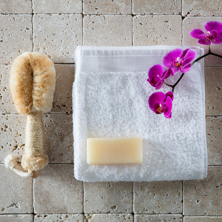 glycerin soap: body care with loofah brush, glycerin soap, white cotton towel with pink orchid set on natural beige limestone for cleansing concept, flat lay, top view Stock Photo