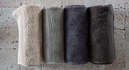 juego de toallas de algodón para hombres hecho de spa de cuatro enrollado tonos beige, verdes, grises y naturales establecidos en la piedra caliza natural de color beige para el fondo cuarto de baño, en plano, vista desde arriba Foto de archivo