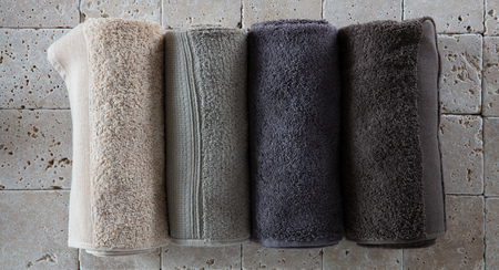 set of cotton towels for male spa made of four rolled up beige, green, grey and natural hues set on natural beige limestone for bathroom background, flat lay, top view Фото со стока - 60680379
