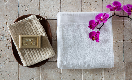 mimos: washing up concept with French mitt, olive oil Marseilles soap, white cotton towel with pink orchid set on pure beige limestone for pampering, flat lay, top view Foto de archivo
