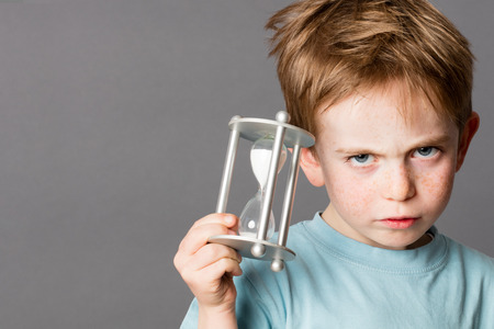 impatience: unhappy little boy with red hair showing his impatience with an egg timer in his hands for time concept, grey background Stock Photo