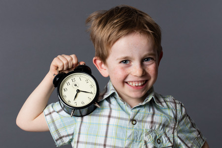 cheerful little boy with red hair and freckles enjoying showing an alarm clock for playful time concept and youth, grey background Stock Photo