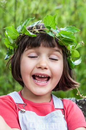 joyous: portrait of a joyous cute little child with a green ivy leaf crown singing with eyes closed, enjoying to dream about playful vacation, outdoors