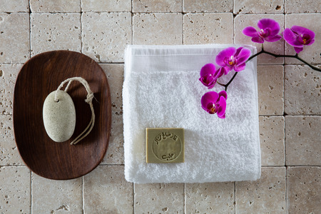 exfoliation: foot care concept with pumice stone, Alep soap, white cotton towel with pink orchid set on natural beige limestone for exfoliation spa, flat lay, top view