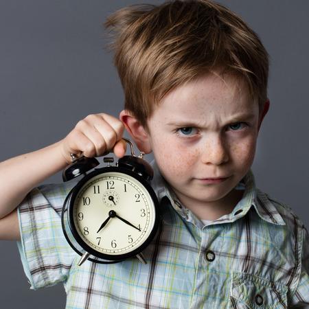 llegar tarde: chico joven disgustado con una mirada oscura reprocharle a alguien que sea tarde, el mal humor en mostrar un reloj de alarma para el concepto del tiempo, fondo gris