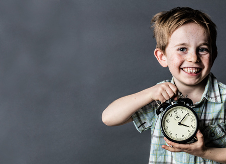 giggling: giggling young child with freckles and missing tooth enjoying showing an alarm clock for time concept and youth, grey background, retro contrast effects with copy space Stock Photo
