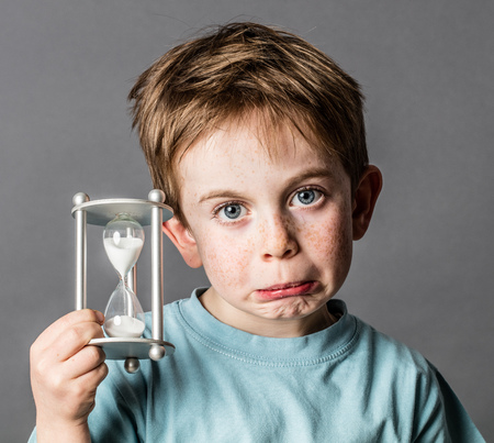 disappointed young boy with disillusioned blue eyes and a pouting mouth holding an hourglass, showing his fear of growing up for time concept, grey background, contrast effects