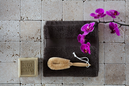 exfoliation: beauty concept with loofah body brush, olive oil Marseilles soap, grey cotton towel with pink orchid set on clean beige limestone for exfoliation, flat lay, top view
