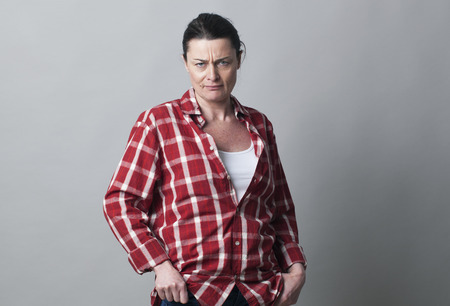 conflicted: annoyed mature woman standing with hands in pockets showing her doubt and disagreement, gray background indoors