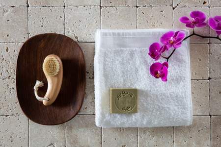 retreat: manicure concept with nail brush, Alep soap, white cotton towel with pink orchid set on natural beige limestone for female retreat, flat lay, top view Stock Photo
