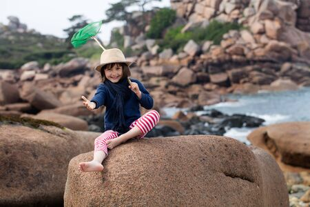 ocean fishing: excited 5-year old child with a hat gesturing, holding a fishing net, enjoying sitting on granite stones for fun outdoors activity in summertime