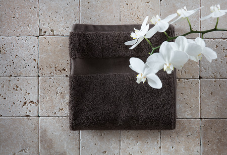 zen freshness still-life with dark grey cotton towel with pure white orchid and limestone background for copy space, flat lay, top view Фото со стока - 63262570