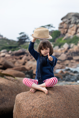 pouting: pouting beautiful young child raising his hat to say hello, showing a thumbs up for relaxing holiday, sitting crossed legs on a giant granite stone on the ocean Stock Photo