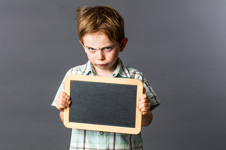 mad young kid holding an empty writing slate to disagree or express his sulking attitude in learning at preschool, grey background indoors Фото со стока - 60951774