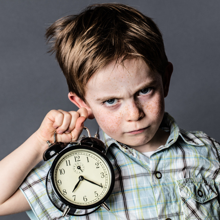 reproach: impatient young boy with a dark look reproaching someone his deadlines, frowning in holding an alarm clock for time concept, grey background, contrast effects