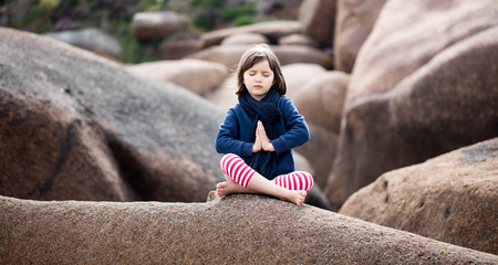spiritual young kid with eyes closed trying to relax, pray and breathe alone for yoga outdoor, seeking for harmony, sitting on giant granite stones, springtime