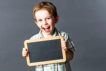 la risa de 5 años de edad reír niño, que muestra una pizarra de escritura vacío, disfrutando de informar a su aprendizaje y bienestar desde el preescolar, fondo gris en el interior