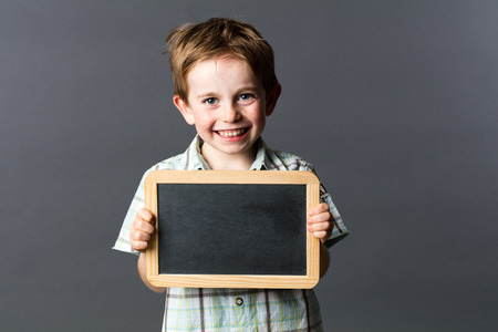 portrait of a happy 5-year old male preschooler proud to learn at school, enjoying holding a copy space writing slate for cheerful education, grey background indoors Фото со стока