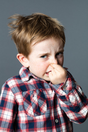 scared young kid holding or pinching his nose for sign of bad odor expressing his annoyance with his face and shoulders, grey background