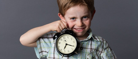 satirical: satirical little kid with red hair and freckles teasing about time, showing an alarm clock for preschooler concept, grey background Stock Photo