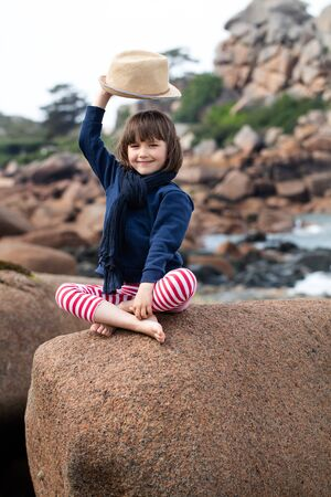 hi hat: vacation postcard concept with smiling young child raising her hat to say hello from her seasonal holiday, sitting crossed legs on a giant granite stone on the ocean Stock Photo