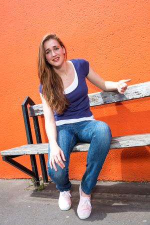 decepci�n: triste hermosa ni�a sentada en un banco, quej�ndose, lamentando algo, expresando la decepci�n o el dolor a trav�s de una pared de color naranja, en exteriores soleados