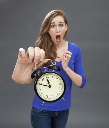 stunned: stunned beautiful young woman standing with an alarm clock in her oversized hand for emphasis on problem on deadlines and time management in the foreground Stock Photo