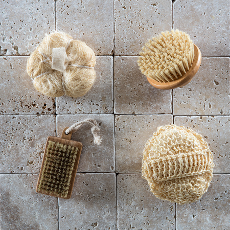 dry clean: body care still-life with loofah sponges, Swedish body brush and nail brush to dry clean and exfoliate set over simple mineral background, flat lay
