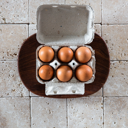 expensive food: simple food ingredient set as expensive life materials with an opened box of six brown eggs set on a round wooden tray over mineral background, flat lay
