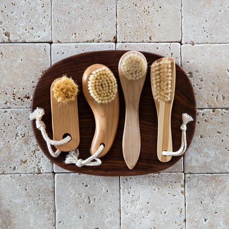 footcare: top view of several stimulating body, face, nail and foot brushes in wooden bowl on pure limestone background for wellbeing concept and wallpaper