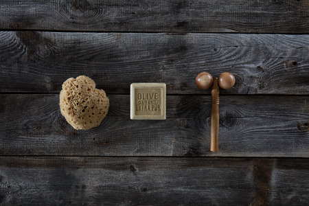 mimos: bodycare and massage products with washing up concept and pampering, natural sponge, organic olive oil soap and wood massage tool over rustic wood background, top view Foto de archivo