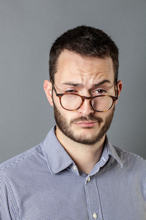 careless: portrait of tired 30s man looking sleepy, indifferent and careless with eyeglasses down, looking clueless at management, grey background, indoor
