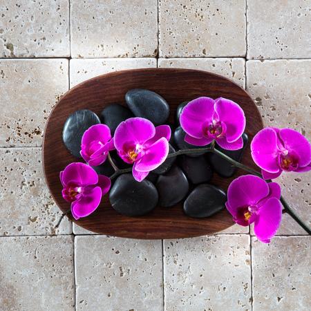 masajes relajacion: en plano para el símbolo de relajación con masajes guijarros negros y orquídeas de color rosa con la madera y la piedra caliza limpia para el papel pintado zen Foto de archivo