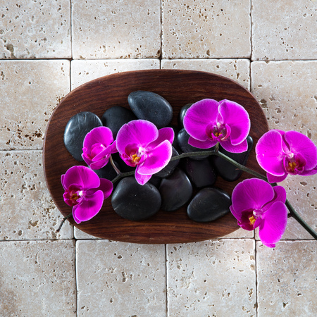 relaxation massage: flat lay for relaxation symbol with black massage pebbles and pink orchids with wood and clean limestone for zen wallpaper