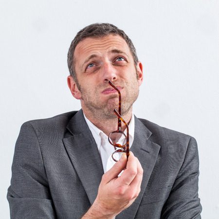 worried middle aged businessman holding his eyeglasses puffing out his cheeks for doubt and confusion in management, white background, indoor Stock Photo