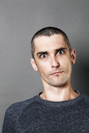 skeptical: portrait of aggressive man looking skeptical, scary and surprised, expressing suspicion and concern, grey background indoor