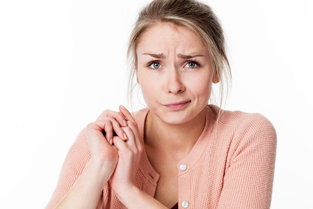 closeup of innocent young blond woman with her hands together, frowning for reflection, apologizing and feeling sorry, white background, indoor Stock Photo