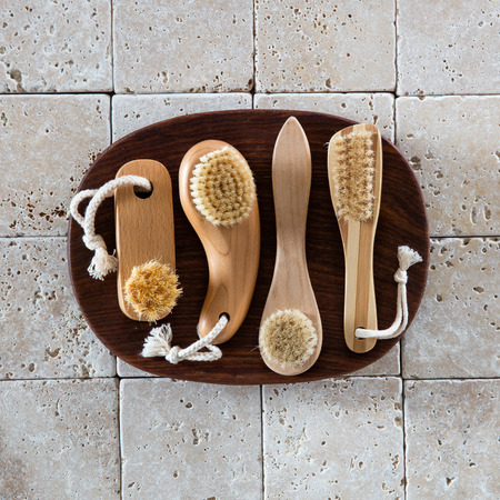 footcare: different exfoliating body, complexion, manicure and footcare brushes in wooden bowl on clean limestone background for beauty spa concept and wallpaper, flat lay