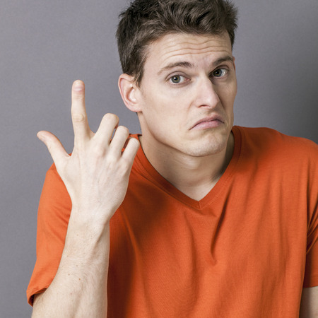 resignation: annoyed handsome young sportsman using his hands to express his doubt and resignation, grey background, indoor