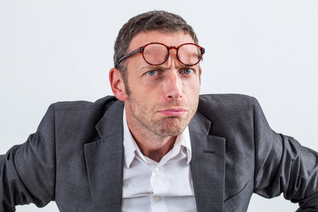 reproach: closeup of unhappy middle aged businessman with eyeglasses on his forehead frowning for suspicion, reproach or attitude, white background, indoor